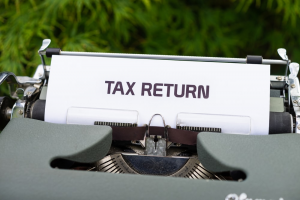 """typewriter with a document stating """"tax return"""""""